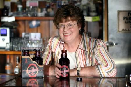 Charlaine Harris, autrice del romanzo che ha ispuirato la serie TV True Blood, posa accanto ai flaconi della omonima bevanda a base di sangue sintetico